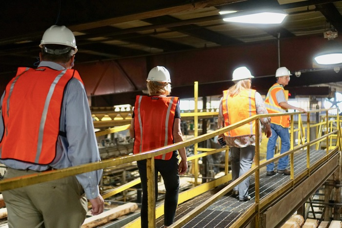 School District representatives tour a lumber mill