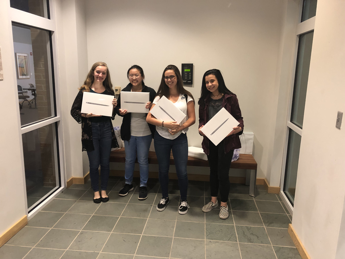 Picture of four students with their MacBooks