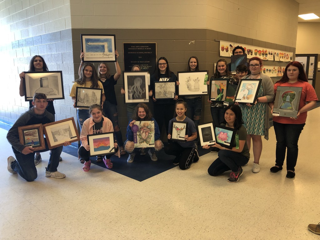 Picture of students with artwork