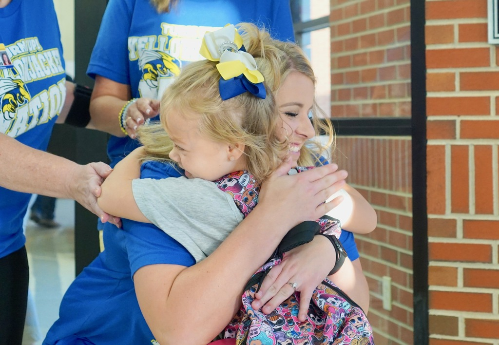 Picture of a teacher hugging a student