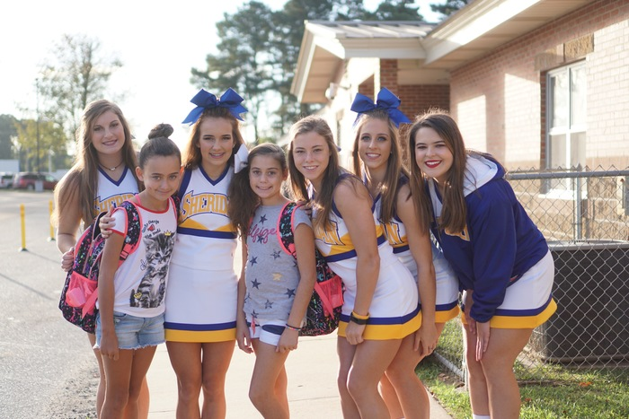 Cheerleaders help with opening up car doors at SIS