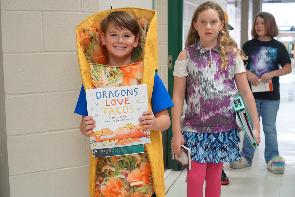 Student dressed up as a taco with his book, Dragons Love Tacos