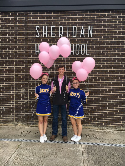 Students posing with pink balloons that will be released later in the evening