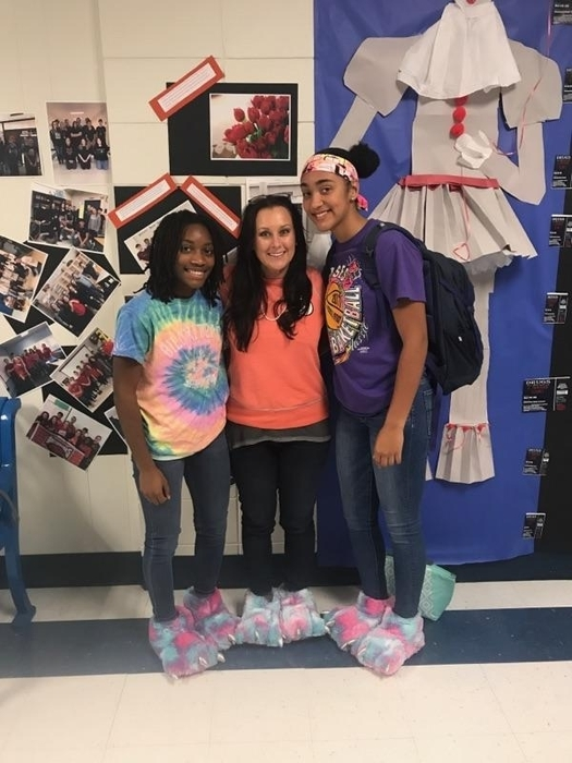 Two students and counselor pose in their matching slippers