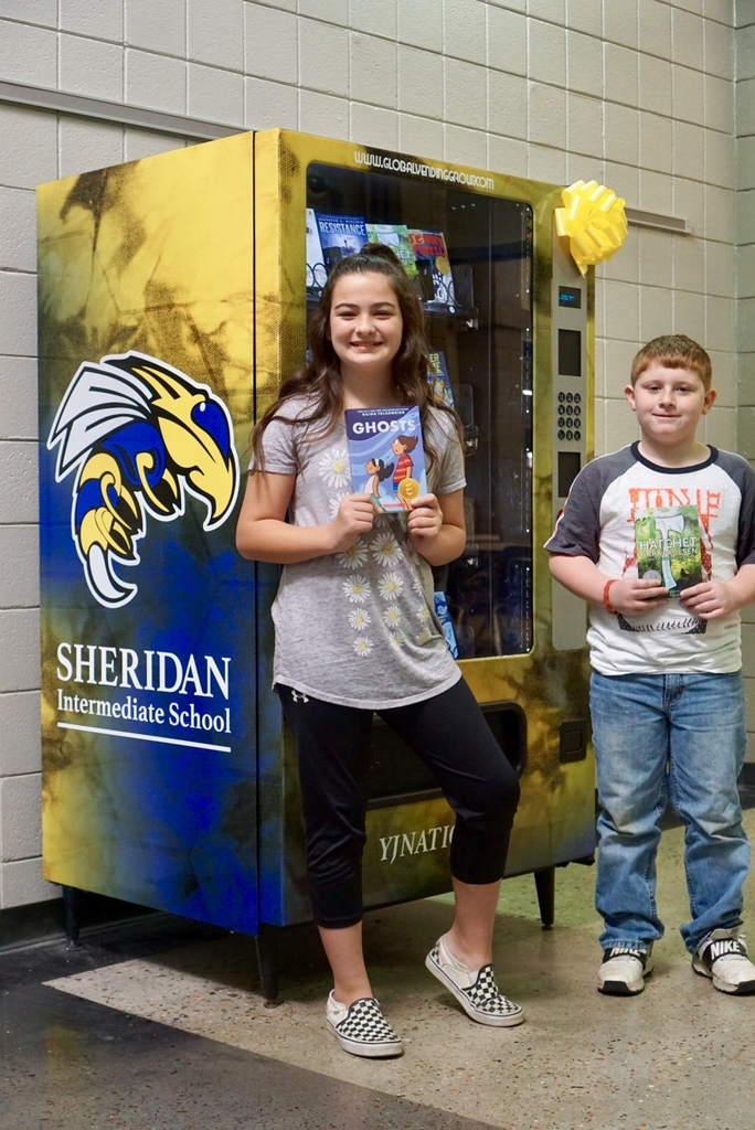 Two students in front of the book vending machine