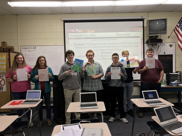 High School students hold up their Thank You letters from their 2nd grade reading buddies