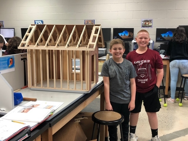 Sam Cypert & Jacob Hutchison with a house they built.