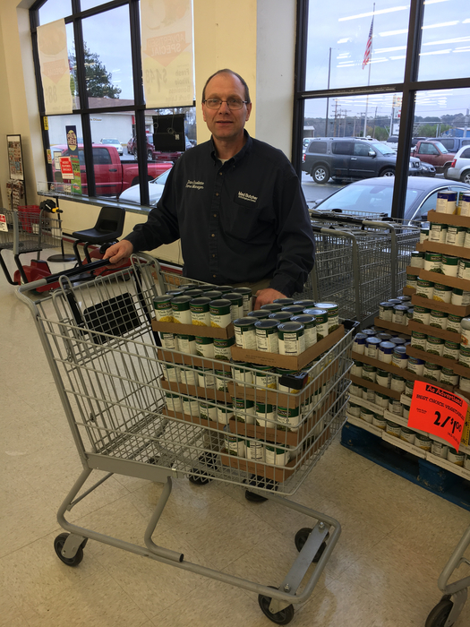 Man posing with his cart full of donated canned goods