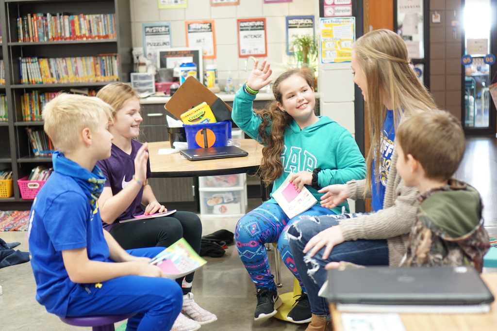 High school student reading to younger students