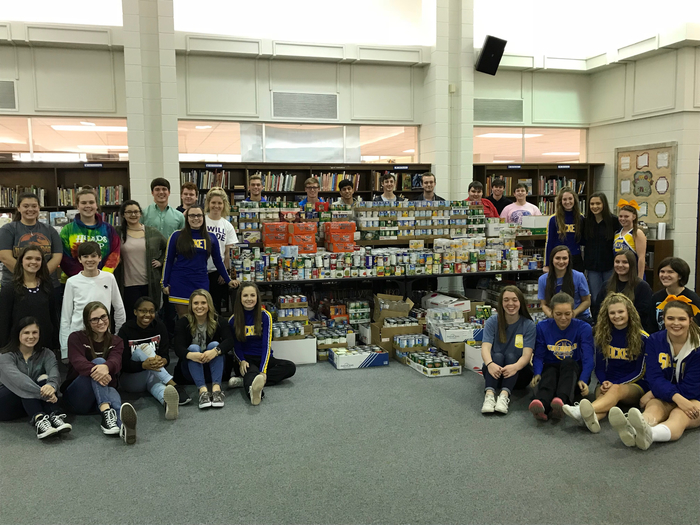 Students posing with cans collected through can drive