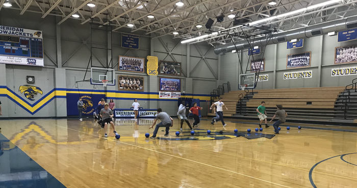 Students running and grabbing dodge balls in the gym