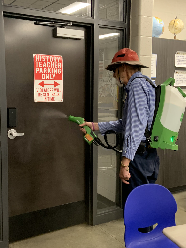 Image of custodian disinfecting our building