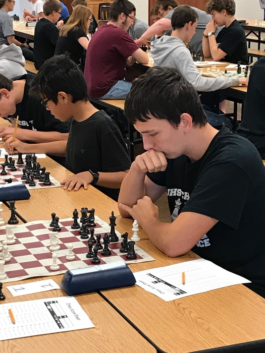 Christian Woods playing chess at regional competition