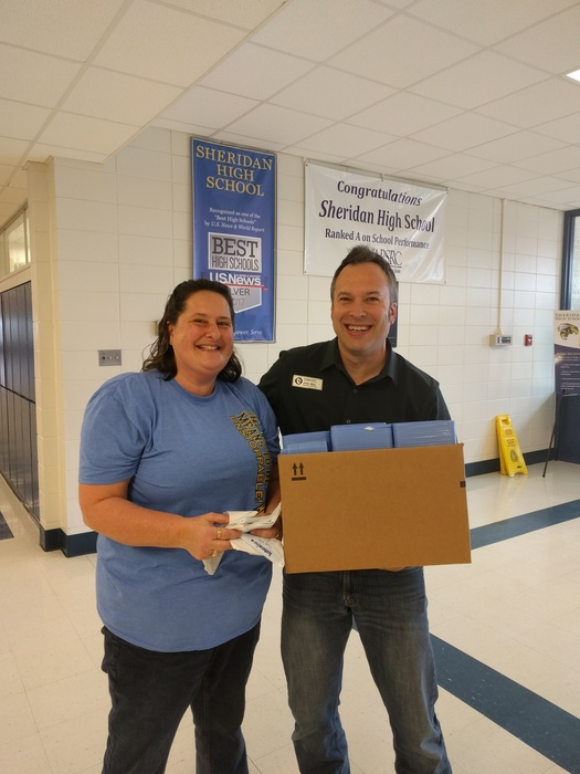 Karen Burnett and Justin Wise holding donated science lab supplies