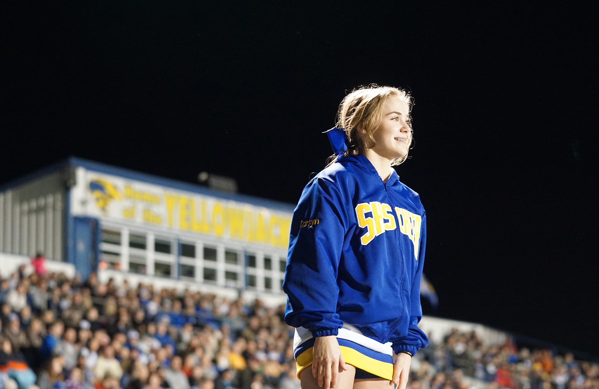 Cheerleader in front of stands