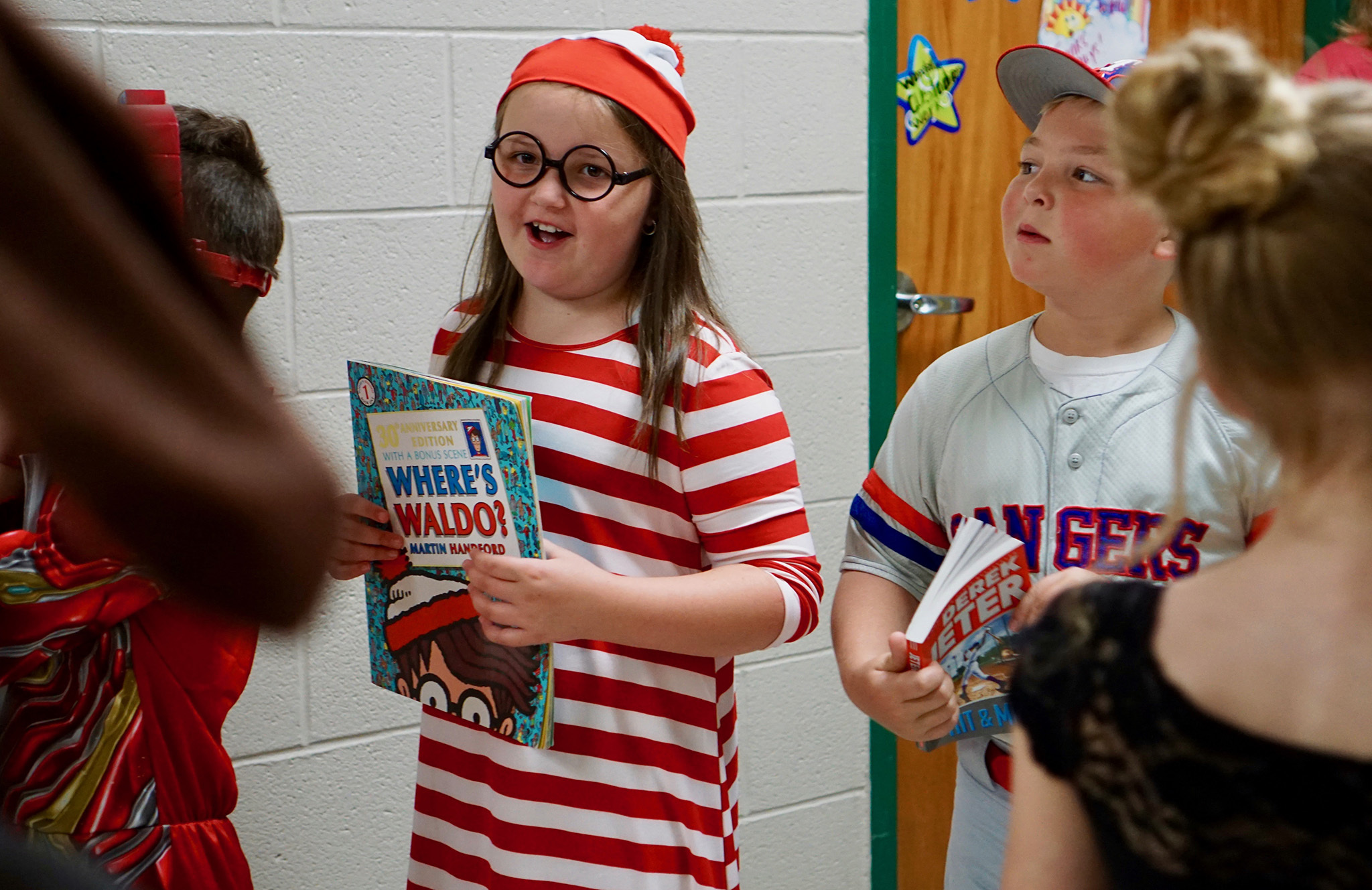 Student wearing a Waldo outfit with a Waldo book