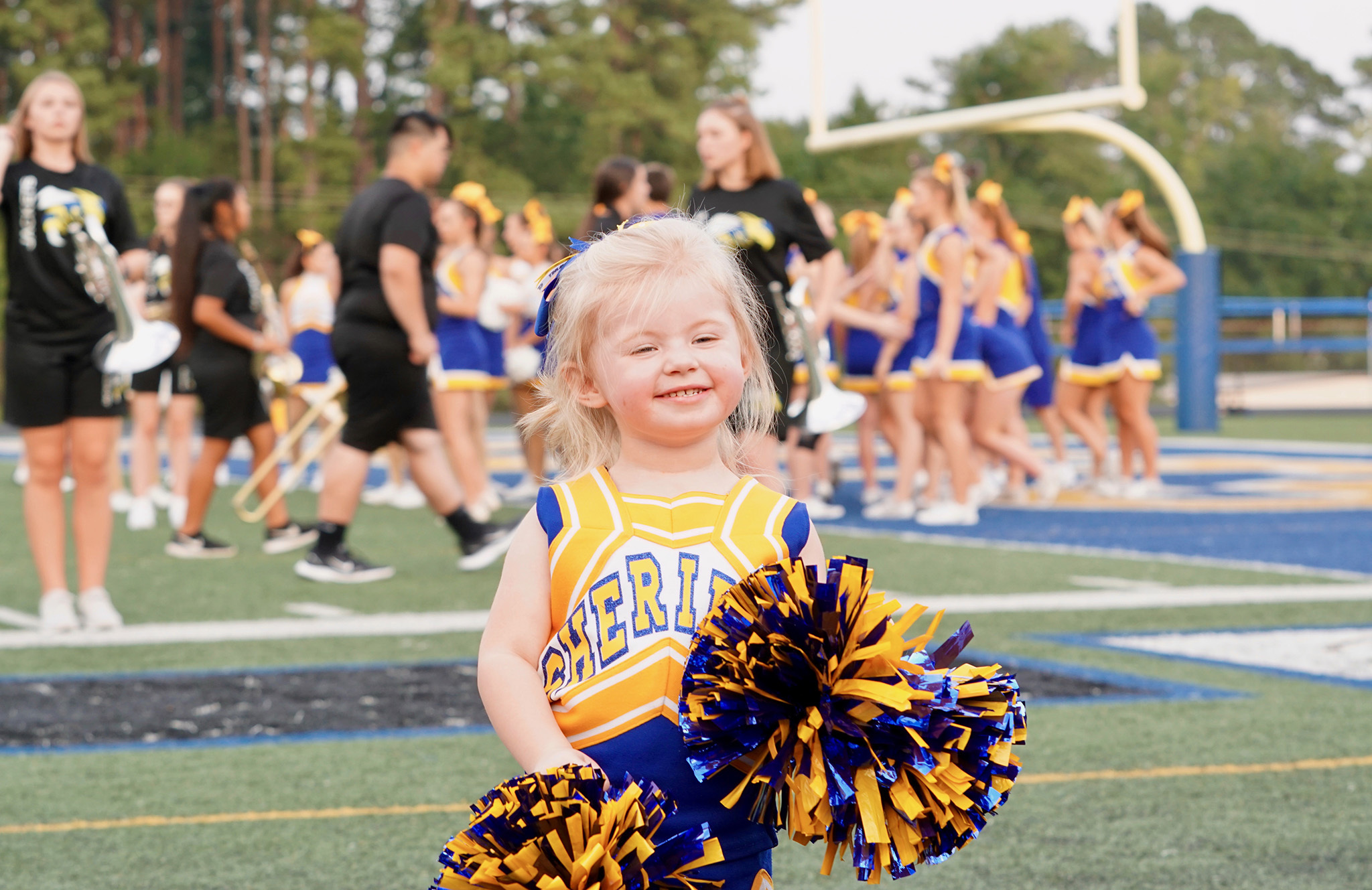 A little girl dressed in cheer uniform