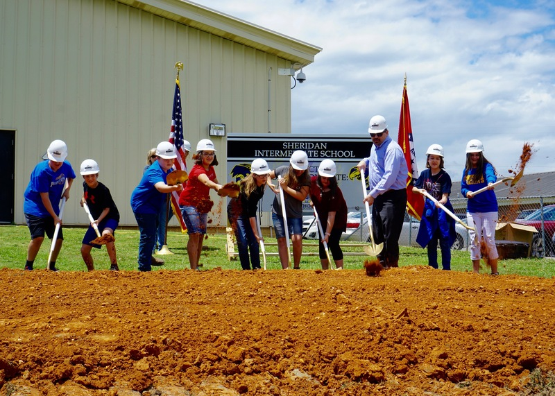 Students shovel dirt at SIS groundbreaking ceremony