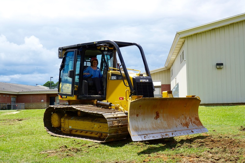 Assistant Principal Teresa Knight operates back hoe at SIS groundbreaking ceremony