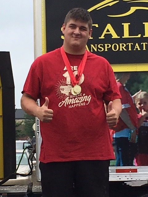 Alex Smith smiling with one of the 3 gold medals he won at the Special Olympics