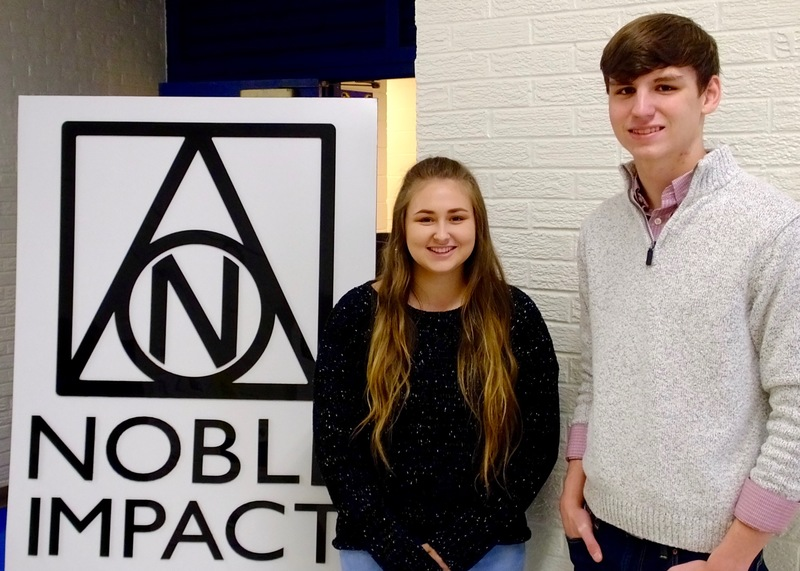 Two Interns Shelbie and Noah pose by Noble Impact Sign