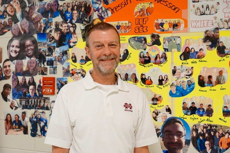 Phil Wesson poses by wall of photos he has taken of his students all year