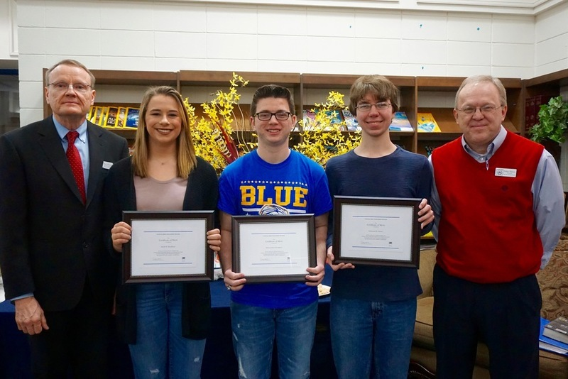Three national merit finalists pose with certificates alongside principal and AP coordinator